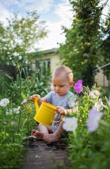 Een kleine jongen zit en houdt een gele gieter in de tuin.