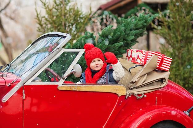 Een kleine jongen zit in de auto van een cabriolet in een rode hoed met een kerstboom