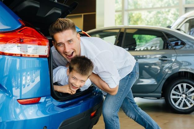 Een kleine jongen zit in de kofferbak terwijl zijn ouders een nieuwe auto uitkiezen.