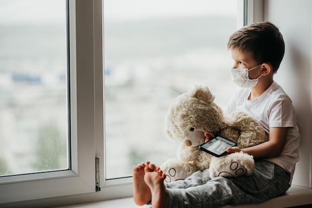 Een kleine jongen zit op een raam met een teddybeer in quarantaine en speelt in een mobiele telefoon. preventie van coronavirus en covid - 19