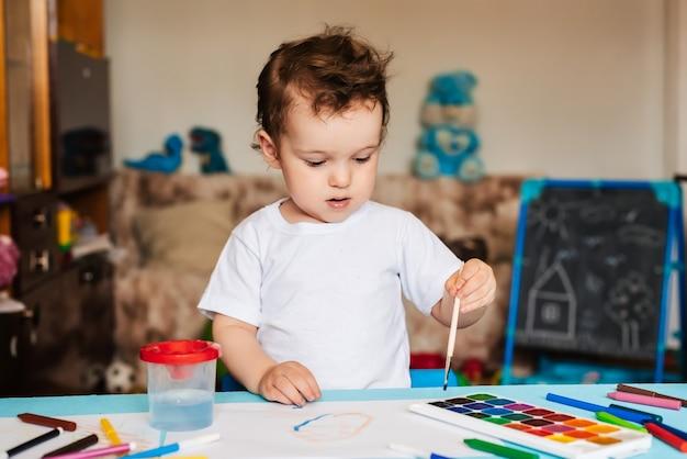 Een kleine jongen zit op een stoel en tekent met gekleurde verf
