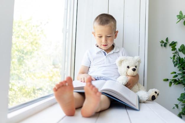 Een kleine jongen zit voor het raam met een boek en een zachte beer