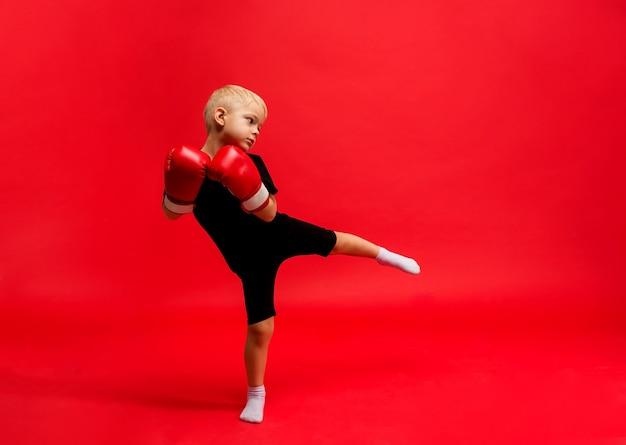 Een kleine jongensbokser staat in bokshandschoenen en maakt een uitval met zijn voet op rood