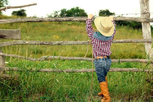 Een kleine jongenscowboy in hoed dichtbij omheining op aard