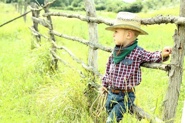 Een kleine jongenscowboy met hoed op de natuur