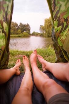 Een kleine kampeertent op het meer, een overnachting en de voeten van een jong stel