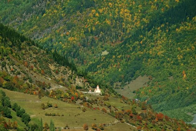 Een kleine kerk op de helling van de berg van de kaukasus in de vroege herfst