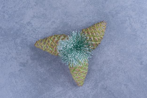 Een kleine kerstboom met dennenappels op een grijze ondergrond
