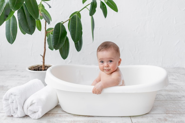 Een kleine kindjongen van 8 maanden oud baadt in een bad met schuim en zeepbellen