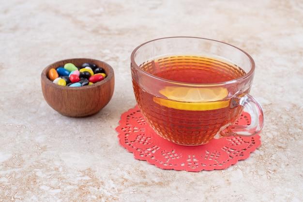 Een kleine kom met diverse soorten snoep en een kopje thee