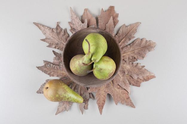 Een kleine kom peren op plataan bladeren op marmer