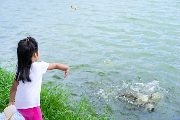 Een kleine meisje voedende vis bij de vijver in openbaar park
