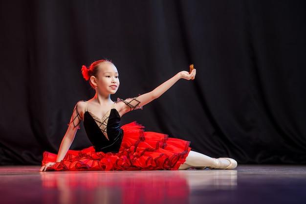 Een kleine meisjesballerina danst op het podium in een tutu op spitzen met castaneda's, de klassieke variant van kitri.