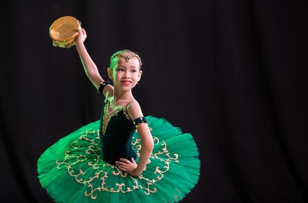 Een kleine meisjesballerina danst op het podium in een tutu op spitzen met een tamboerijn, een klassieke variant van esmeralda.