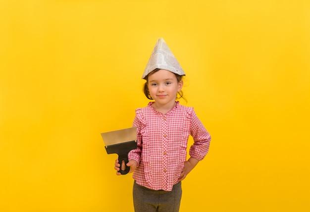 Een kleine meisjesbouwer in een document hoed met een metaaltroffel op geïsoleerd geel