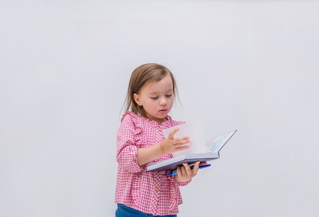 Een kleine meisjesleerling met een blocnote en pen op een geïsoleerd wit