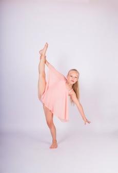 Een kleine meisjesturner in een sportzwempak voert een pose uit van ritmische gymnastiek op een witte geïsoleerde muur