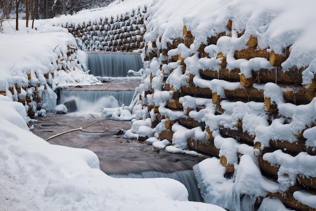 Een kleine muur van kleine boomstammen omsluit een kleine bergstroom met watervallen in een winterbos in de buurt van kale bomen in de karpaten