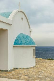 Een kleine orthodoxe kerk aan de oevers van de middellandse zee. cyprus.