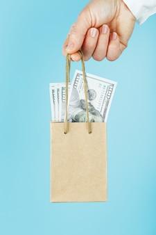 Een kleine papieren zak voor financiële hulp en ondersteuning gemaakt van papier op arm's length met amerikaanse dollars op een blauwe achtergrond. het concept van verwaarloosbare financiële steun in het bedrijfsleven,
