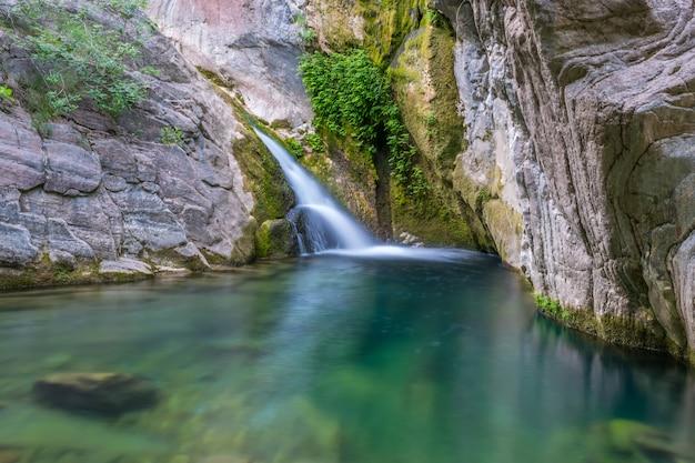 Een kleine pittoreske waterval in een gezellige berglagune