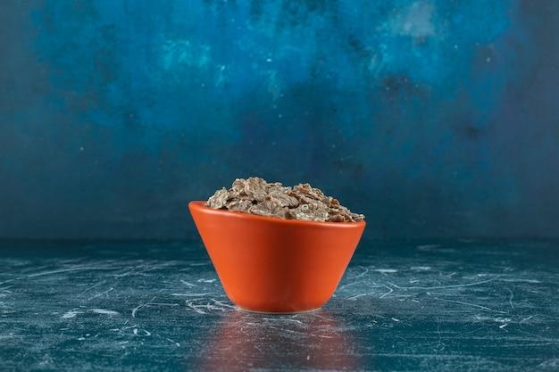 Een kleine portie droge cornflakes, op de blauwe achtergrond. hoge kwaliteit foto