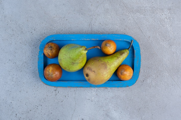 Een kleine portie peren op een blauwe schotel op marmeren achtergrond.