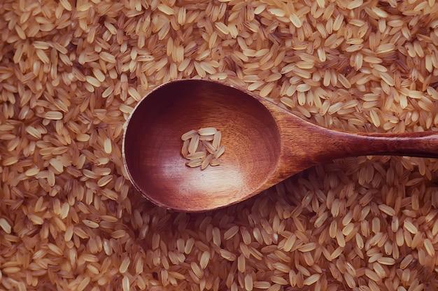 Een kleine portie rijst in een houten lepel op de achtergrondstructuur van de rijst. rode rijst met een houten lepel close-up.