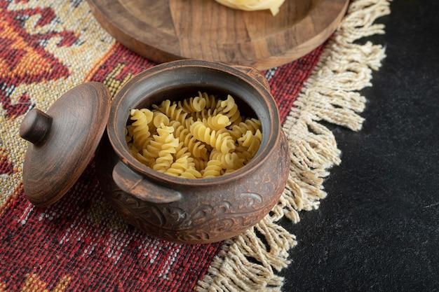 Een kleine pot onvoorbereide spiraalvormige verse macaroni