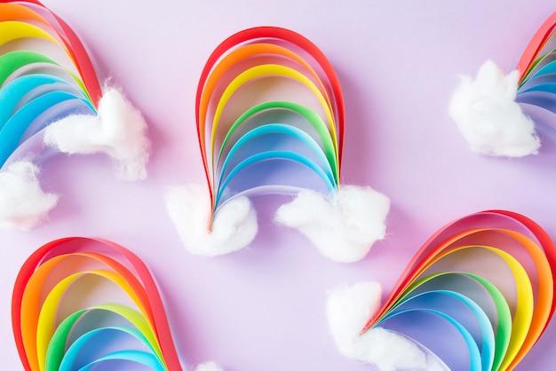 Een kleine regenboog van gekleurd papier met sneeuwwolken, creativiteit met hun handen op een lichte achtergrond. diy