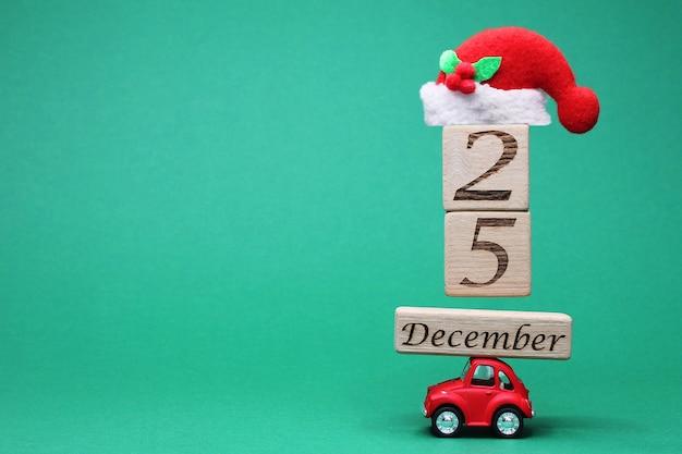 Een kleine rode speelgoedauto met 25 december op houten blokken en een kerstmuts erop.