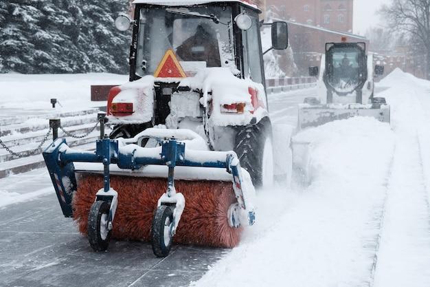 Een kleine rode tractor met een borstel veegt sneeuw van het trottoir bij de muren van het kremlin tijdens zware sneeuwval.
