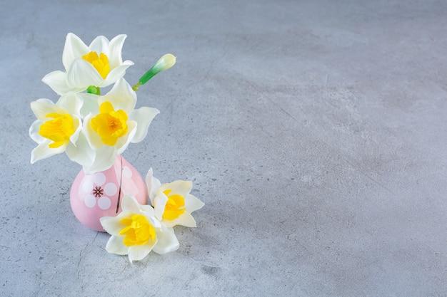 Een kleine roze vaas vol witte bloemen op een grijze achtergrond.