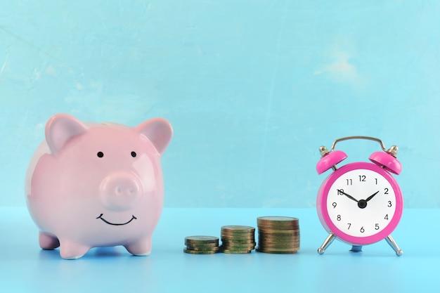 Een kleine roze wekker, drie stapels munten en een spaarvarken op blauw