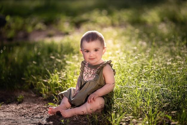 Een kleine schattige baby met kort haar, in een groene jurk, zit op het gazon in het gras bij het pad, kijkt in de zon naar de lucht. ze lacht naar haar familie. gelukkige jeugd, loop in het park. zomer