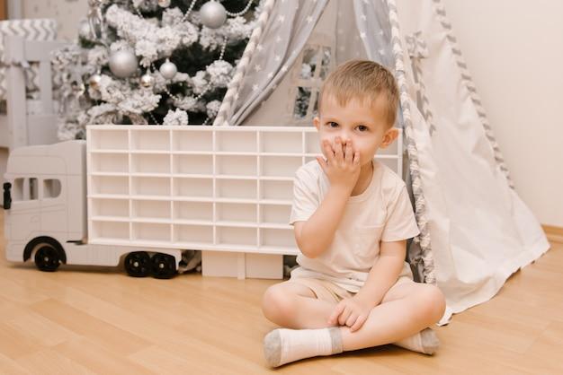 Een kleine schattige babyjongen zit in een kinderkamer in een wigwam en blaast een kus naast een kerstboom en een houten auto