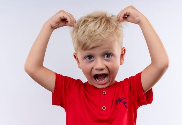 Een kleine schattige blonde jongen in een rood t-shirt die zijn haar met vingers vasthoudt terwijl hij op een witte muur kijkt
