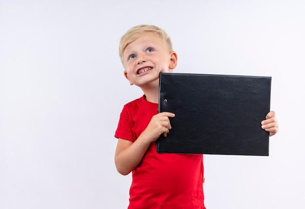 Een kleine schattige blonde jongen in een rood t-shirt glimlachend en met lege map terwijl hij omhoog kijkt op een witte muur