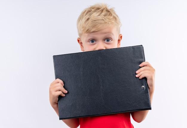Een kleine schattige blonde jongen in een rood t-shirt glimlachend en met lege map terwijl hij op een witte muur kijkt