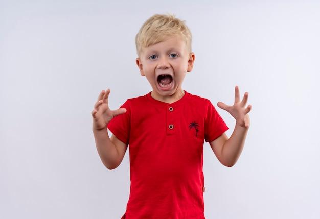 Een kleine schattige blonde jongen in een rood t-shirt schreeuwt met zijn handen omhoog terwijl hij op een witte muur kijkt