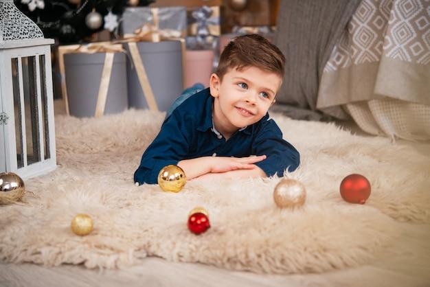 Een kleine schattige jongen ligt op een pluizige sluier in een gezellige, huiselijke nieuwjaarssfeer. baby wacht op kerstmis