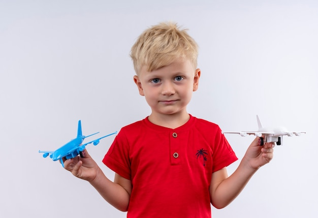 Een kleine schattige jongen met blond haar en blauwe ogen, gekleed in een rood t-shirt met een blauw en wit speelgoedvliegtuig terwijl hij op een witte muur kijkt