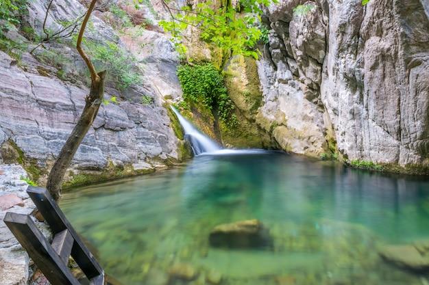 Een kleine schilderachtige waterval in een gezellige berglagune.