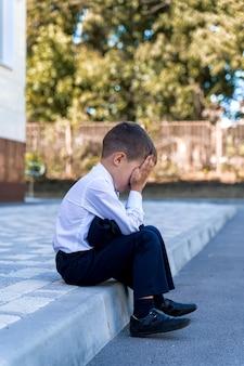 Een kleine schooljongen huilt op school