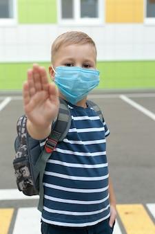Een kleine schooljongen met een masker tijdens een uitbraak van coronavirus en griep