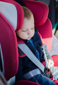 Een kleine slapende jongen in een autostoeltje. de jongen slaapt in een rode autostoel. veiligheid van kinderen in de auto.