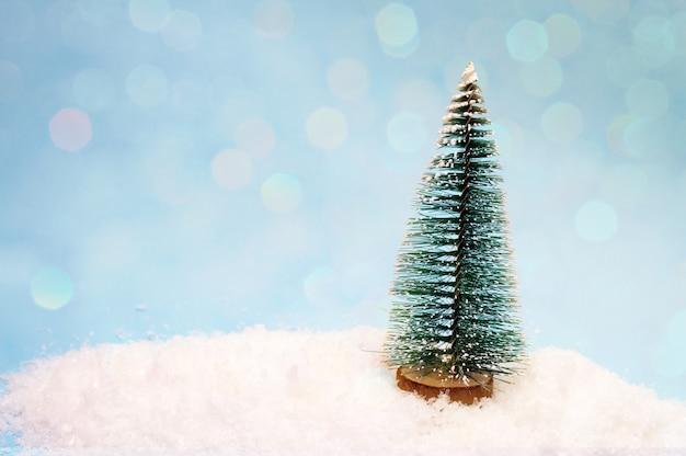 Een kleine speelgoedboom in de sneeuw