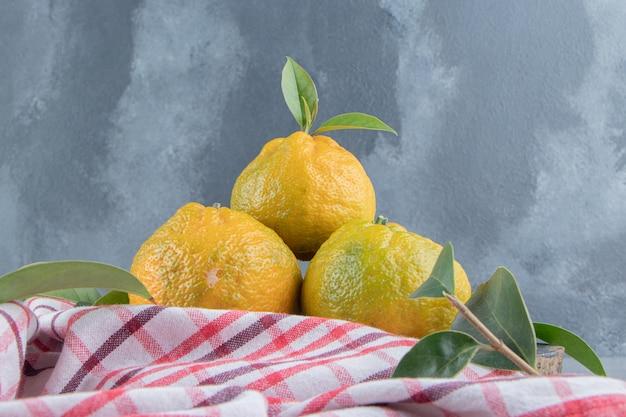 Een kleine stapel mandarijnen op een handdoek op marmer.