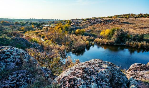 Een kleine stapel oude stenen in een groot groen geel veld tegen de achtergrond van een fantastisch mooie blauwe lucht