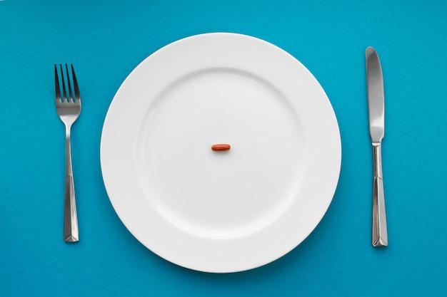 Een kleine tablet op een bord. medisch. eet pillen in plaats van voedsel.